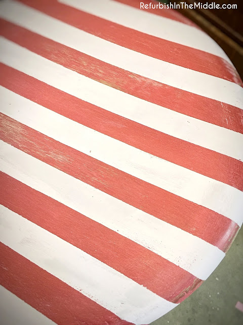red and white stripes on the seat of a wood stool