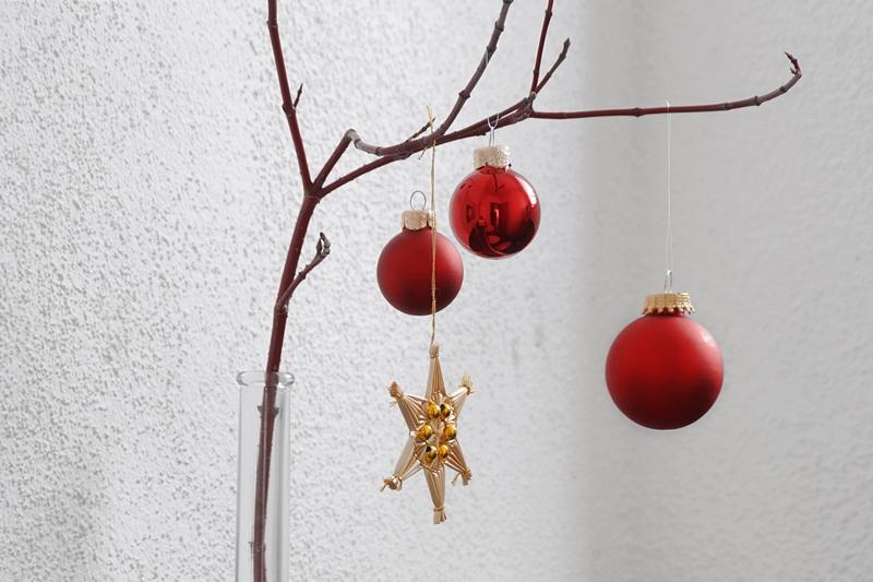 Weihnachtsdeko klassisch traditionell modern, Zweig mit roten Kugeln und Strohstern dekoriert