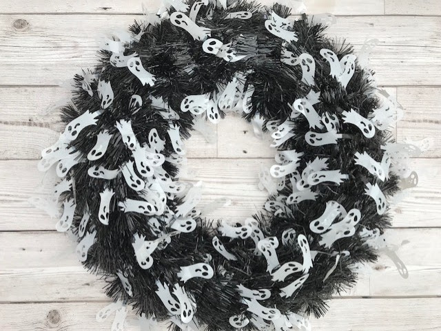 A black tinsel wreath with white ghost figures on it