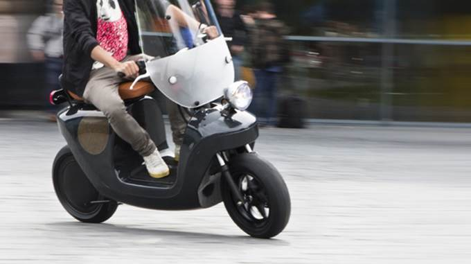 man rides electric scooter