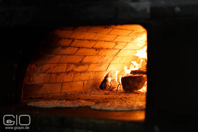 Brick oven with fire and pizza