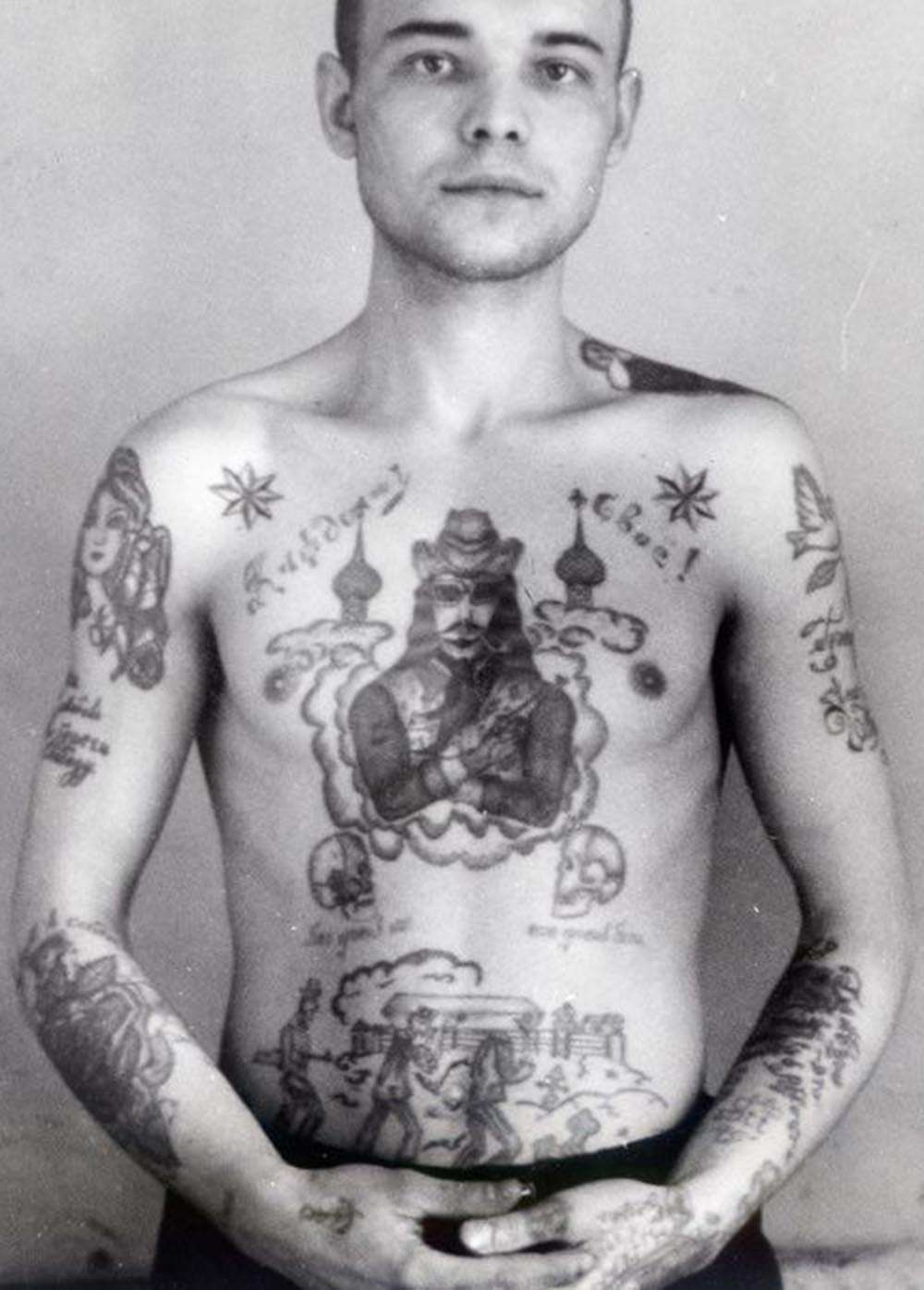Text on the right arm reads 'Save love, keep freedom.' Text on the left arm reads 'Sinner.' Text across the chest reads 'To each his own.' Text underneath the skulls reads 'God against everyone, everyone against God.' Text on the wrist in German reads 'Mein Gott' (My God). A cowboy with a gun shows this thief is prepared to take risks and is ready to exploit any opportunity. A dove carrying a twig (left shoulder) is a symbol of good tidings and deliverance from suffering.