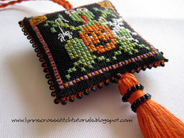 Halloween cross stitched scissor fob tutorial showing black beaded scissor fob with pumpkins embroidered  in cross stitch