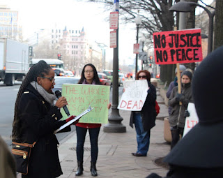 image of demonstration outside Department of Justice office. A woman wearing a coat and scarf with long braids, brown skin, and glasses holds a mic and a clip board in front of 3 people holding protest signs.