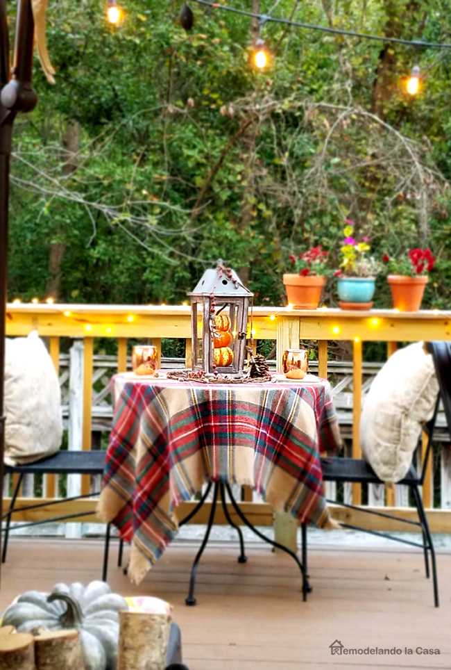 Patio bistro set decorated for Fall with lantern full of pumpkins, lights and plaid tablecloth