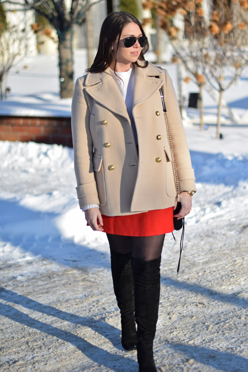 Tan peacoat with red mini skirt on young adult woman.