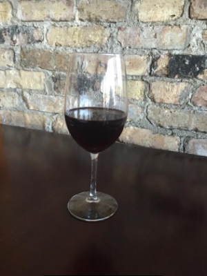 Wine glass with exposed brick background at 1913 Restaurant and Wine Bar in Roselle, Illinois