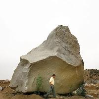 Büyük bir kaya parçasının önünde küçücük kalmış bir adam