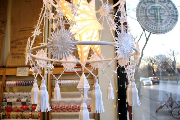 Details of a hand-constructed pajaki including white paper tassels, stars and snowflakes
