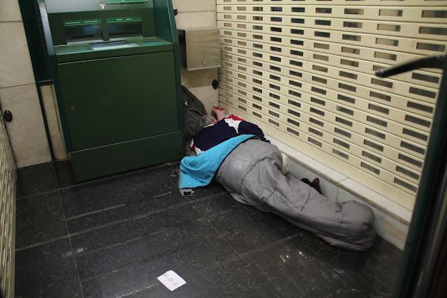 Una persona sin hogar duerme en un cajero