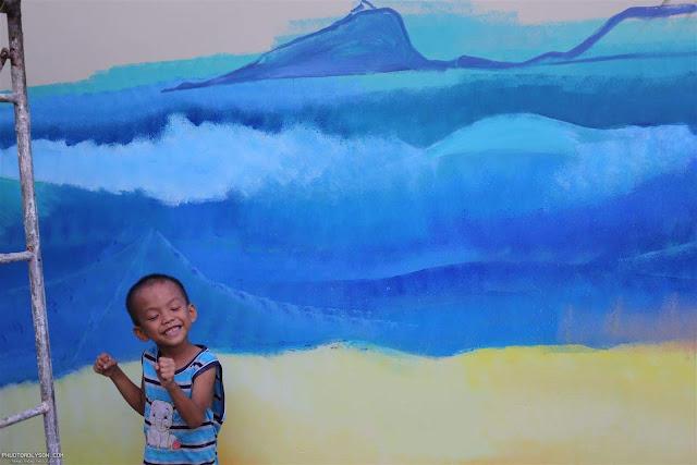Niềm vui của một em bé trên đảo Lý Sơn khi ngắm bức tường mới.