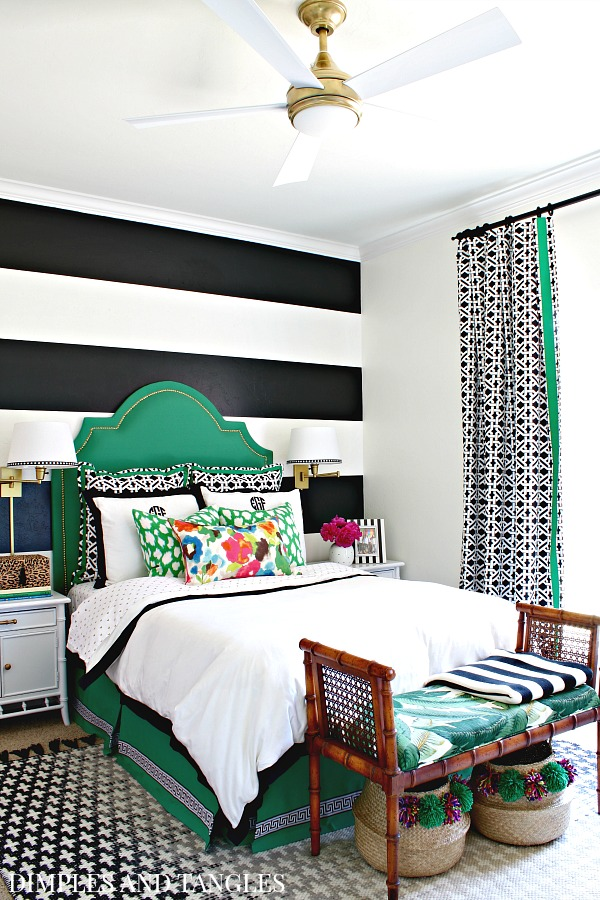 green upholstered headboard, black and white striped wall, black and white curtains, wall sconces, black crosses rug, teen girls bedroom