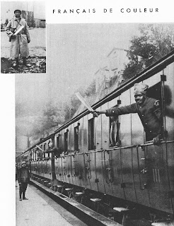 On the far left corner of the image is a small black and white photo of an African man standing in a winter military suit. He is holding a thick white stick in his right hand. The rest of the image is a black and white photo of a train. From one of the windows, an African man in French military suit is standing, putting his arm out to wave a white stick. He is wearing a turban.