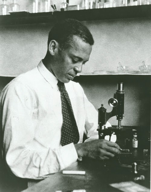 A black and white photograph of an African American man looking at a microscope.