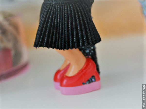 close up of pleated black skirt on Miss Piggy character heel