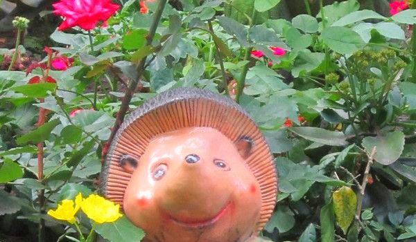 Statue of smiling hedgehog among flowers