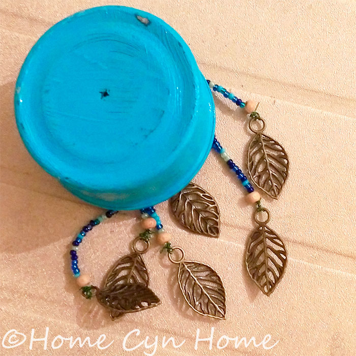 a few tin cans, glass beads and brass pendants will make for a lovely wind chime on a budget