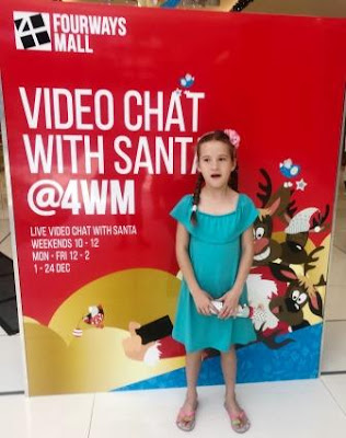 Girl in front of banner: Video Chat with Santa