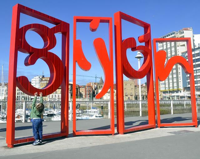 las letronas: son las letras que forman el nombre Gijón, estan divididas en 4 cuadrados, g, ij, o, n grandes de metal de color rojo están en el puerto deportivo, se ven veleros, se ve al fondo el palacio revillagigedo. Pixelillo de espaldas intentando subirse a la letra G