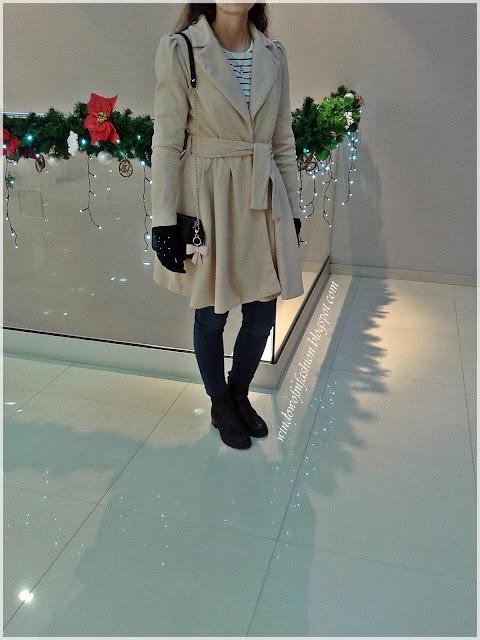 Beżowy płaszcz, bluzka, jegginsy, czarne botki, czarna torebka na łańcuszku, granatowe rękawiczki, naszyjniki z Mikołajem