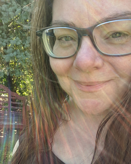 image of my face in close-up, with my hair down and wearing grey-framed glasses, standing in my garden with a lens flare creating the look of my having rainbow-streaked hair