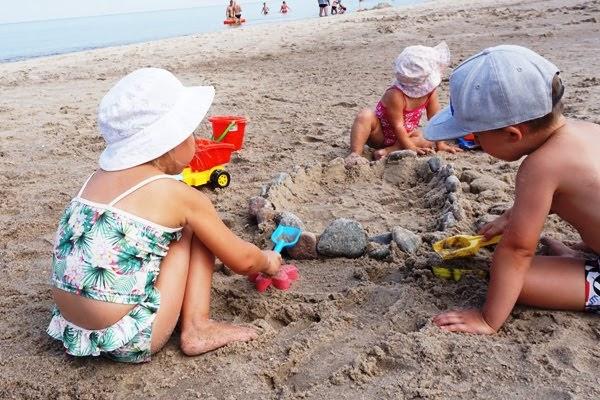 trójka dzieci bawi się współnie nad morzem