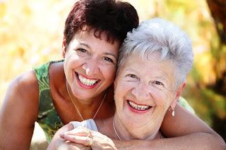 hija abrazando madre mayor, sonrientes