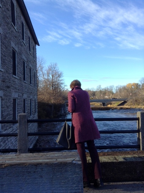 On the dam at the Manotick Mill, Manotick Ontario. Coat Max Mara, NYDJ burgundy pants, All Saints bag.