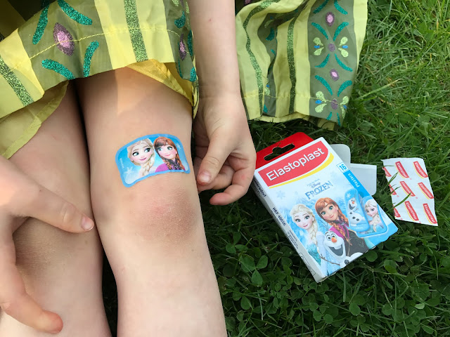 A close up of big sister's knee with an Elastoplast sticker with Elsa and Anna from Frozen on it