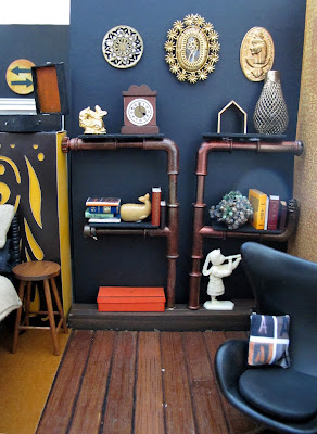 One-twelfth scale miniature lounge area with a set of pipe shelves containing books and ornaments and a black egg chair.