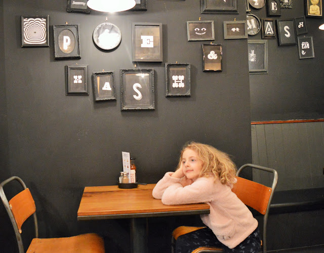 a young girl sat at a table with photoframes in the background.