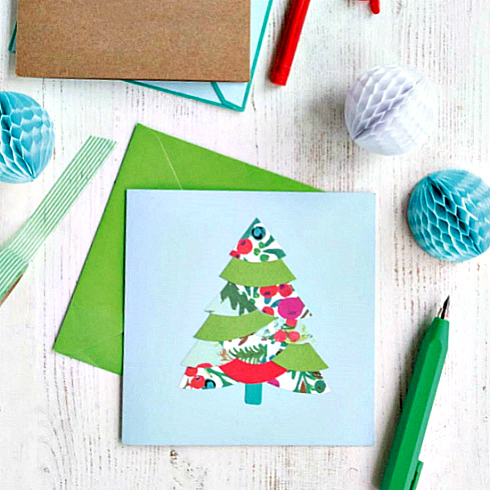 A square Christmas card featuring a collaged tree composed of solid and patterned paper shapes