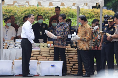 "President Joko ""Jokowi"" Widodo (center) checks a package of confiscated drugs"