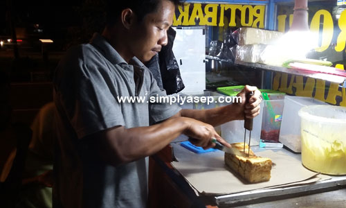 MEMOTONG : Kang Nunun sedang asyik memotonhg motong dua tangkup roti bakar pesanan saya  (16/3).  Foto Asep Haryono