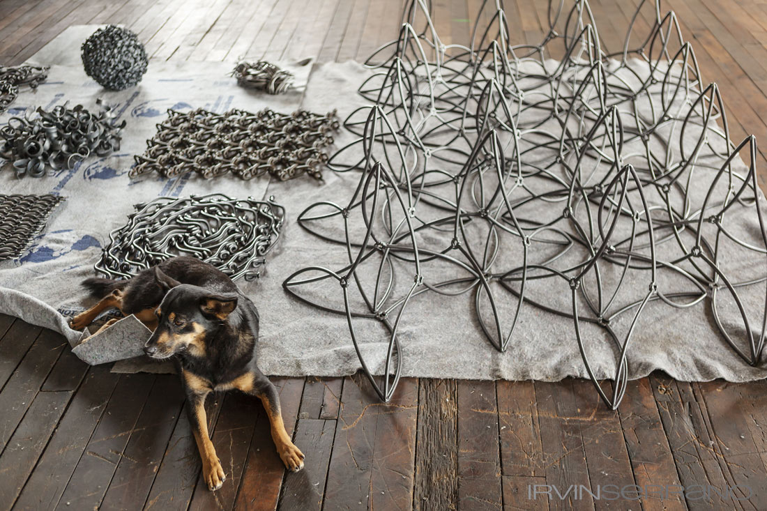 A dog lays in front of scupltures made entirely of nails and created by John Bisbee at his studio in Brunswick Maine.
