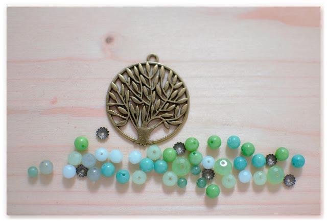 pendentif arbre bronze vieilli sur lit de perles vertes et turquoises