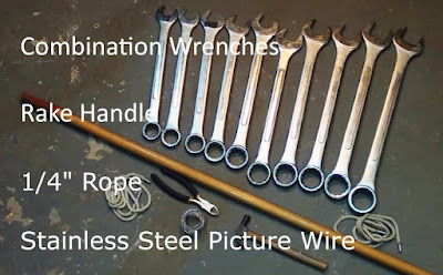 "Set of combination wrenches, rake handle, 1/4"" rope, stainless wire and text stating same"