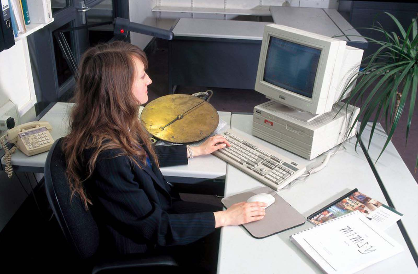 Sue Julian-Ottie, a collections system data manager, using a database computer. Her hair is long and natural, with side-swept bangs. She wears a dark, striped suit jacket. 1996.