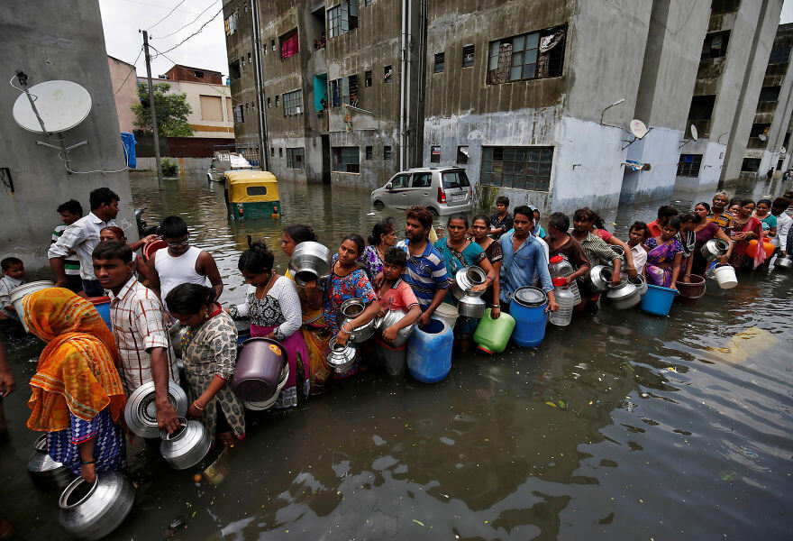 18 Devastating Pictures Of The Flooding In South Asia That Will Shock You - People Wait In A Line To Collect Drinking Water From A Municipal Tanker At A Flooded Residential Colony In Ahmedabad, India