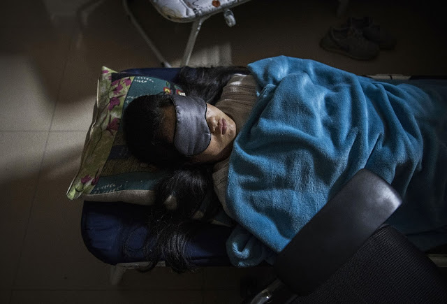 A Huawei employee sleeps in her cubicle in the research and development area