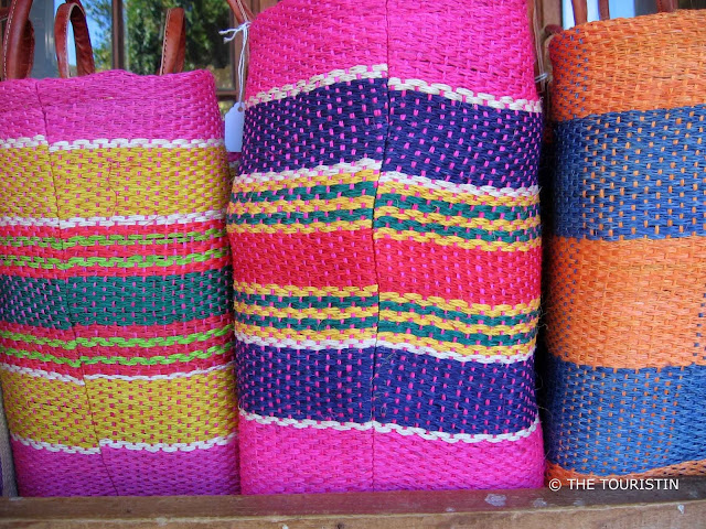 Pink, yellow, white, red, green, orange and blue coloured baskets in a row of three..