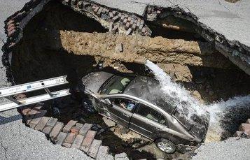 Auto en un socavón de carretera
