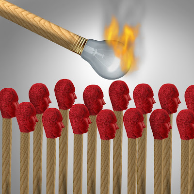 Figurative illustration of burning light bulb match about to set light to lots of matches with red human-shaped tops