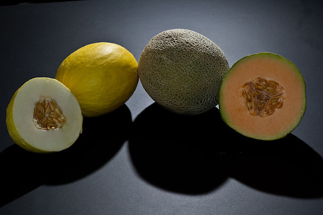 Complete and half cut melons on a table