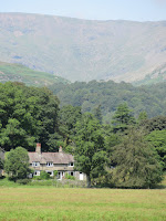 coniston water of a beautiful house set into the mountain side - by: © Paul c Walton