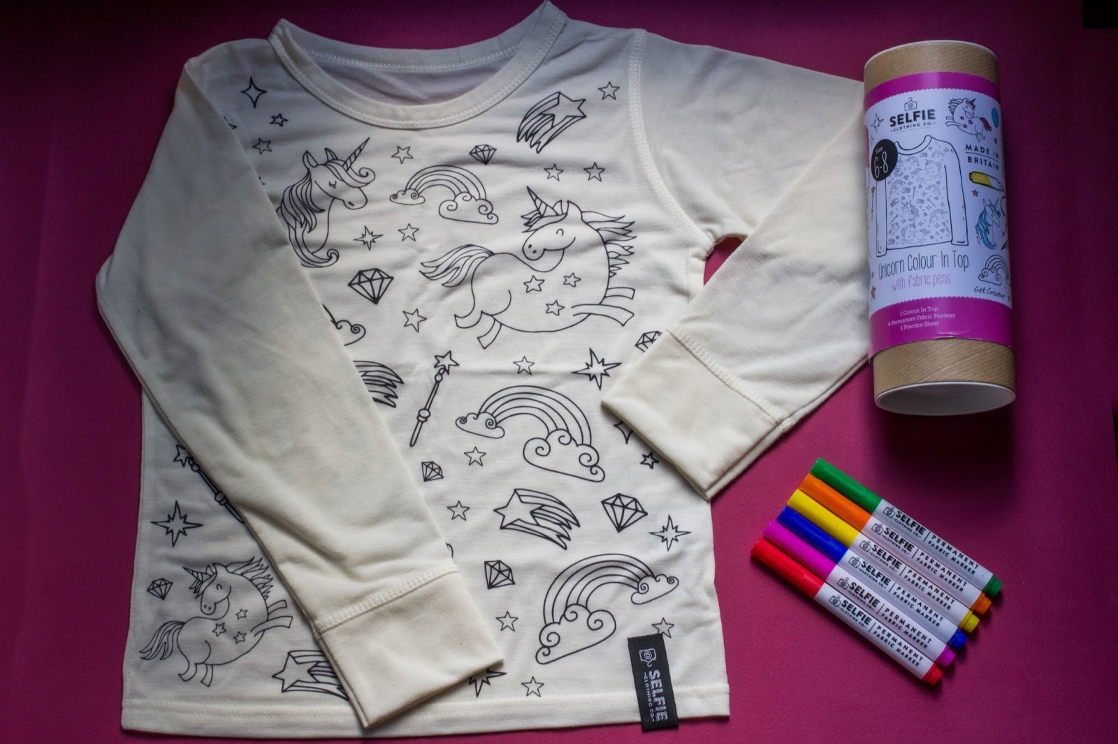 A long sleeve cream top with outlines of stars, unicorns and rainbows on, 6 fabric pens and the tube packaging
