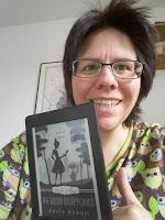 das Bild zeigt die Buchbloggerin mit dem Kindle in der Hand. Das Cover zeigt die Silhouette von Jill und ihrem Kater