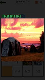 на берегу моря установлено несколько палаток на закате