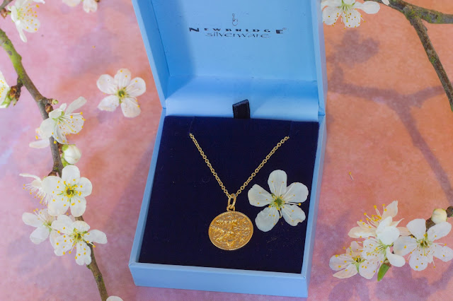 Sun Moon and Stars gold necklace from Newbridge Silverware surrounded by blossom on a pink plaster capture by lucy background