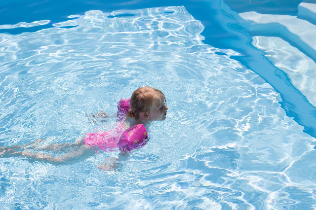 A young girl in a pink swimming costume and arm bands swimming in a pool